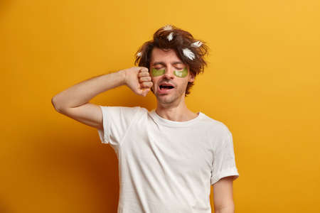 Photo of young man with messy uncombed hair, collagen pads under eyes, yawns early in morning, needs more sleep and rest, hates Monday awakening, dressed in casual clothes, isolated on yellow wall