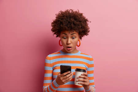Astonished surprised curly young woman stares at smart phone display, sees something amazing online, reads disturbing insulting message, drinks takeout coffee, poses against pink background. Stock Photo