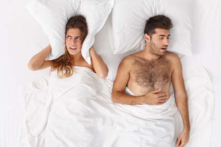 Couple in bed. Depressed young woman covers ears with pillow, cant sleep because of mans snoring, has sleepless night, lies irritated in bed. Family, bed time, insomnia, sleep problems concept Stock Photo