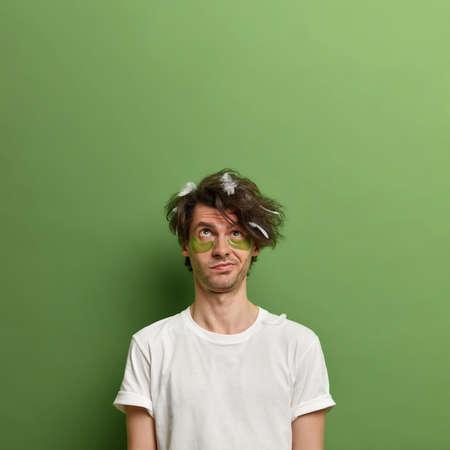 Thoughtful man concentrated above, waits for nice effect after applying collagen patches under eyes, has uncombed hair with feathers, poses against green background, copy space for your promotion