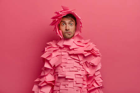 Puzzled young man bites lips and looks surprisingly at camera, reacts on astonishing news, makes funny costume of stickers, poses indoor against bright pink wall. Human facial expressions concept Фото со стока