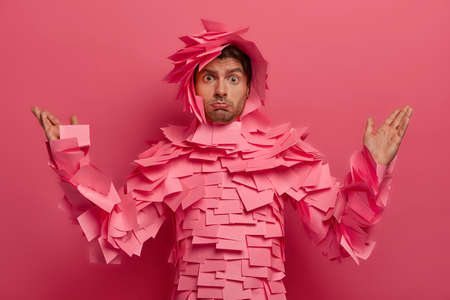 Puzzled indignant unshaven man raises hands, purses lower lip, looks with displeased expression, covered by sticky notes, isolated on pink background, dissatisfied hearing something unpleasant