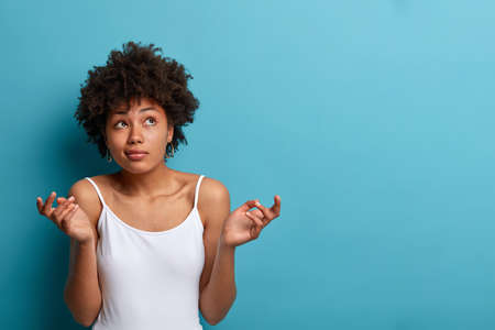 Clueless perplexed dark skinned woman with curly hair shrugs shoulders and looks questioned upwards, raises hands in hesitation, dressed casually, poses against blue studio background, copy space