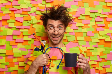 Professional male engineer holds cables, ready to plug in computer, gives you help with modern technologies, drinks coffee, smiles positively, sticks out head from paper wall with colored stickers