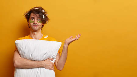 Confused unaware man raises hand doubtfully, feels bewildered, cannot remember his dream, holds soft pillow, has under eye treatment with collagen patches, poses over yellow wall with empty space