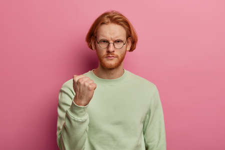 Outraged bearded man with bob hairstyle, clenches fist, frowns from insult and displeasure, expresses anger, argues with someone, threatens or warns, dressed in casual jumper, isolated on pink wall