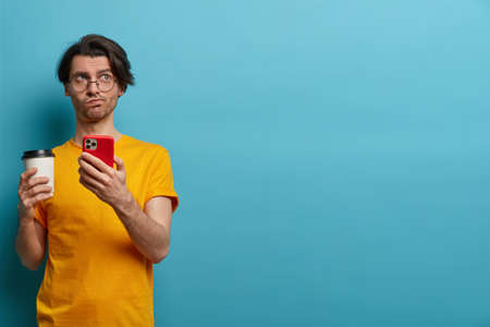 Thoughtful European man with trendy hair, uses mobile phone for browsing, got message and contemplates about something, drinks coffee from disposable cup, wears yellow t shirt, stands indoor