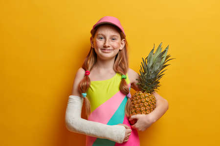 Lovely small girl in colorful bathing suit and cap, poses with pineapple against yellow background, enjoys summer time and good rest, has broken arm after falling from height or dangerous sport