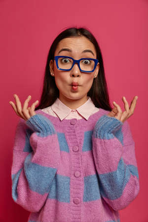 Funny playful woman mimicking fish, raises hands, shows her hilarious side, fools around, wears square spectacles and striped jumper, has childish expression, poses indoor against pink background