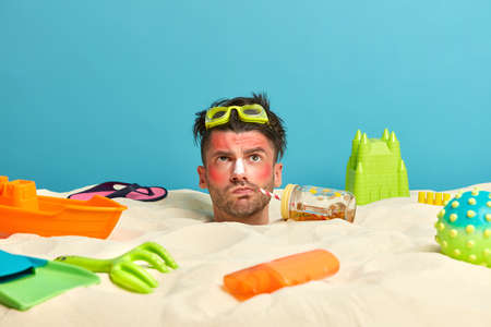 Head of man with thoughtful expression, buried in sand, drinks refreshing beverage, uses sunblock, spends much time at sandy beach near sea, got very bad sunburn, surrounded by different items