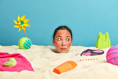 Sea resort and tourism concept. Surprised woman looks away, keeps head over beach sand, has red skin after sunburn, recreats at seaside with various necessary things around, needs sun protective cream