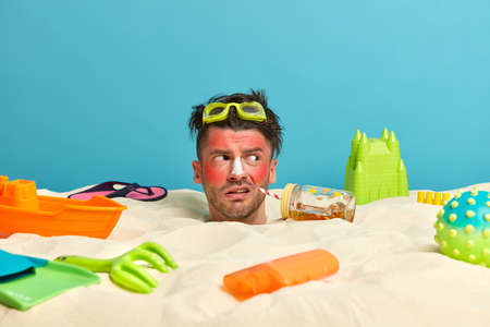 Outdoor shot of unhappy young man got sunburn in very hot summer day, drinks cold beverage, applies sunscreen and looks away, buried in sand on beach, surrounded with different items for rest