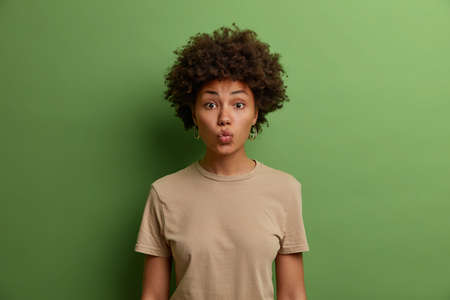 Attractive dark haired woman keeps lips rounded, expresses her satisfaction, wants to kiss someone, wears casual brown t shirt, poses against green background. Human facial expressions concept Zdjęcie Seryjne