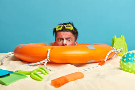 Serious man buried in sand, stuck head in lifebuoy, spends free time at beach, poses over blue sea, surrounded with toys and suncreen bottle, has damaged skin from sun. Hello summer holidays