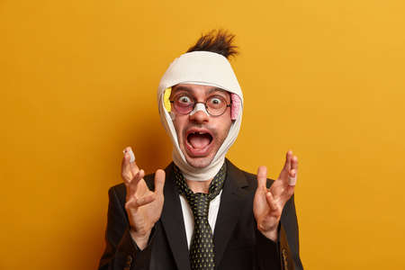 Photo of crazy man with bandaged head, injured swollen face and bruise under eye, recovers after accidental fall or car crash, gestures actively, dressed in formal outfit isolated on yellow background