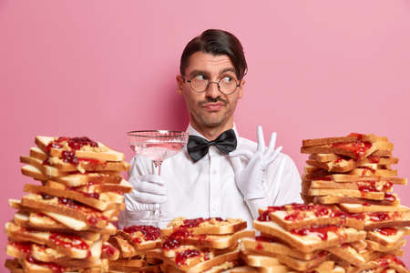 Elegant pensive waiter touches bowtie, dressed in snow white uniform, suggests to degustate new cocktail, looks aside thoughtfully, poses near pile of delicious bread toasts. Bartender at work