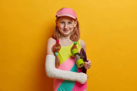 Beautiful carefree girl with two pony tails, glad after riding skateboard, wears cast on broken arm, dressed in bathing suit and cap, spends free time in skatepark, isolated on yellow background