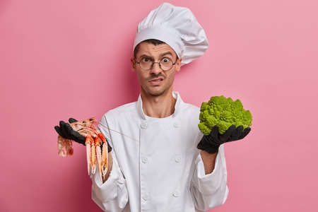 Displeased cook in white uniform, works at restaurant, given task to cook dish from broccoli and crayfish, wears black gloves, prepares dinner, isolated over pink background. Gastronomy concept