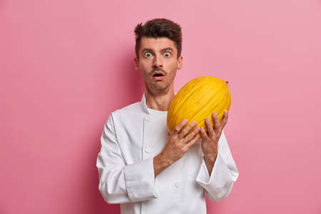 Stunned emotional male cook holds delicious sweet ripe melon, going to prepare tasty dessert, stares at camera with shock, wears uniform, isolated on pink background. Healthy eco food, organic farming
