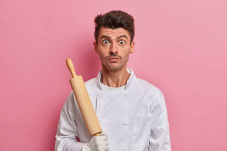 Surprised chef with kitchen tool, dressed in white uniform, busy baker holds rolling pin, ready for making dough, isolated on pink background. Male cook going to make cake first time. Baking, recipe