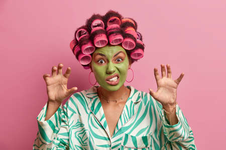 Indoor shot of housewife makes angry grimace, raises hands like paws, clenches teeth, wears hair rollers, beauty mask for rejuvenation, dressed in domestic clothes. Women, skin care, cosmetology.