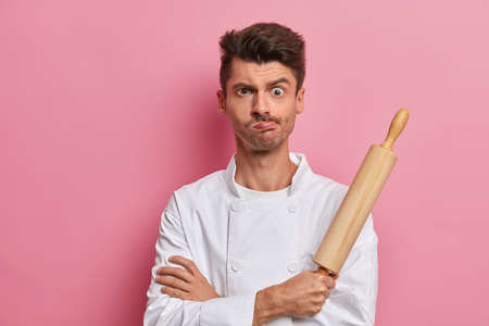 Indoor shot of male cook looks with displeased sullen expression, holds rolling pin, feels tired after cooking at kitchen, poses against pink background, prepares homemade food, restaurant cuisine