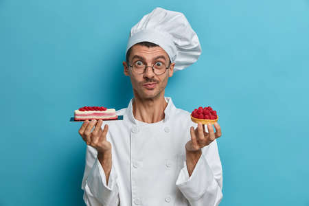 Cooking, profession, bakery concept. Young male cooker holds tasty confectionery, desserts decorated with berries, poses at restaurant kitchen, isolated over blue background, has creative occupation
