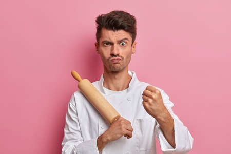 Serious angry chef clenches fist, gives instruction for cook, holds rolling pin, works on professional kitchen, going to make pastry, wears white uniform, isolated on pink background. Cooking time
