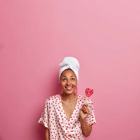 Vertical shot of pleased smiling woman has dark skin, holds delicious appetizing lollipop, wears towel and pajama, concentrated above isolated on pink background. Young lady holds sweet candy on stick
