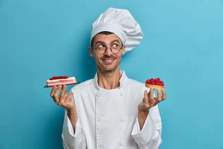 Confectioner man stands with delicious cakes, has nice ideas how to decorate pastry, poses against blue background, wears white uniform. Professional pastry chef at kitchen. Bakery, confectionery Stockfoto