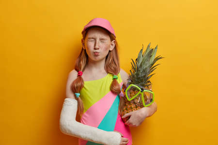 Little girl with two pony tails, freckled face, closes eyes and makes funny grimace, has fun during summer holidays, wears bathing suit and cap, holds pineapple with snorkeling mask broken arm in cast