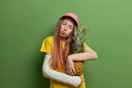 Portrait of adorable little freckled girl tilts head, has eyes closed and lips rounded, embraces delicious pineapple with love, has broken arm after falling from height, isolated on green background. Stok Fotoğraf