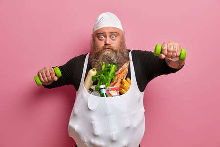 Fat motivated man goes in for sport, poses with high calorie food, demonstares resistance to temptation, looks with bugged blue eyes at camera, isolated over pink background. Overeating, weight loss Stok Fotoğraf
