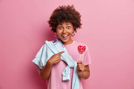 Studio shot of happy surprised dark skinned woman indicates at herself, asks question, holds delicious lollipop, wears sweater tied over shoulder isolated on pink wall. Teenager poses with sweet candy