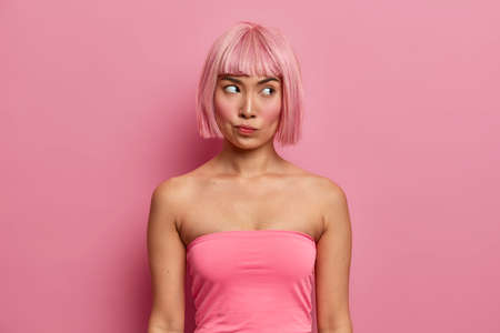 Photo of serious displeased woman with bob hairstyle, dressed in pink top, looks aside pensively, seriously thinks about offer, finds way how to solve troublesome situation, ponders decision 版權商用圖片