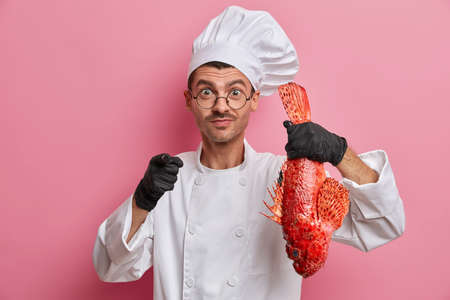 Professional male chef holds big red uncooked fish, suggests to cook delicious meal for you, points at you, wears white uniform rubber gloves poses indoor against pink background prepares seafood dish Stock fotó