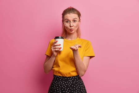 Pretty romantic girl sends only love, keeps lips rounded, palm directed to camera, sends mwah, holds takeaway coffee, dressed casually, poses against rosy background. Tenderness and flirt concept