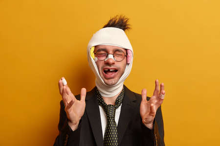 Emotional bruised adult man shouts and raises hands, has brain concussion, wrapped wound head in bandage, missing teeth after unhappy accident, dressed formally, isolated on yellow background.