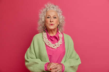 Charming romantic mature wife sends air kiss to husband, stills loves him passionately, cares about herself, wears stylish green jumper and necklace, being on pension, isolated on pink background