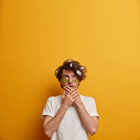 Scared young man covers mouth, looks above, applies collagen patches for reducing fine lines, dressed in white t shirt, isolated on yellow background. Blank space upwards for your promotion.