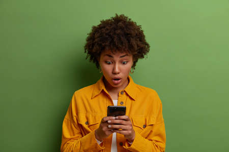 Oh gosh. Stunned dark skinned woman with curly hair stares at display of smartphone, reads shocking news in internet, gasps from wonder, wears yellow jacket, poses against vivid green background