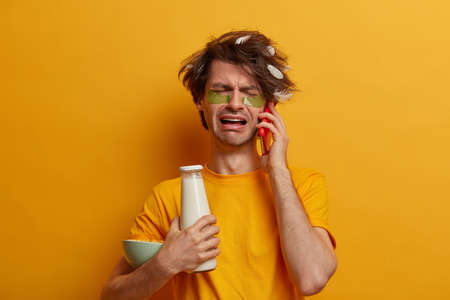 Morning time, daily routine concept. Desperate miserable man with feather on hair, cries while talks on cellular, holds cereals with milk for breakfast, undergoes beauty treatments, reduces wrinkles Stock fotó