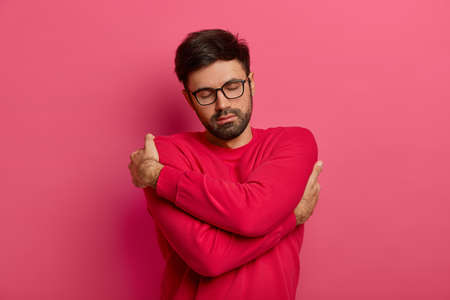 Gorgeous calm bearded man hugs himself, keeps arms around his shoulders, keeps eyes closed, wears soft red jumper, transparent glasses, isolated on pink background, feels coziness, being chilly