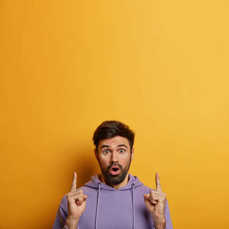 Photo of stunned emotional man with thick beard stares in disbelief and points finger upwards, opens mouth from amazement, demonstrates copy space for your advertising, isolated on yellow wall Imagens