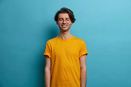 Positive calm relaxed man teenager stands with closed eyes and toothy smile, satisfied with successful finished work, cant sigh from reveal, wears casual summer yellow t shirt, poses indoor.