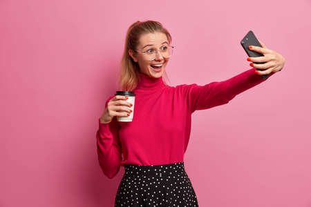 Upbeat millennial girl records video, takes selfie on modern smartphone, calls friend via mobile application, drinks coffee to go, starts day with refreshing beverage, recommends followers best cafe