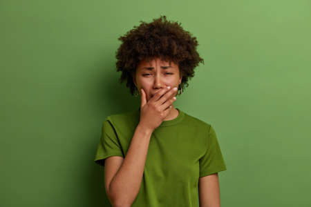 Upset stressful woman in despair, feels depressed, sobs or whins loudly, cannot stop crying, faces troublesome situation, stands grieved against vibrant green background. Negative emotions concept