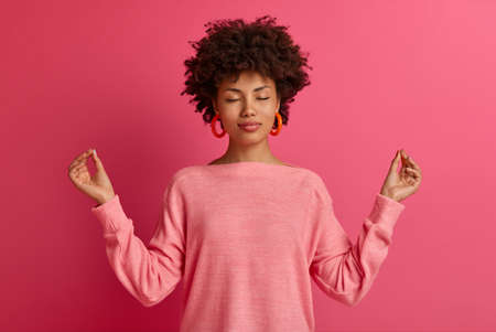 Relaxed curly haired woman meditates and makes yoga exercises, raises hands sideways in lotuse pose, closes eyes and reaches nirvana, wears casual jumper, isolated over bright pink background