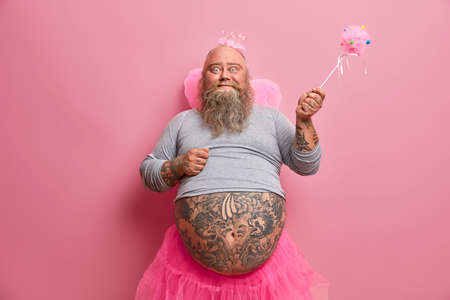 Happy celebration, fantasy, family fun party concept. Positive friedly looking plump man comes from world of fairies, makes your dreams come true, has different activities with children on child show