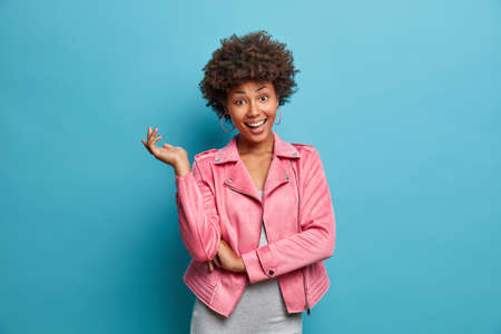 Tender happy young African American woman in pink jacket raises hand, shows perfect white teeth, rejoices good news, has curly hair, poses against pink background. People and emotions concept Banque d'images